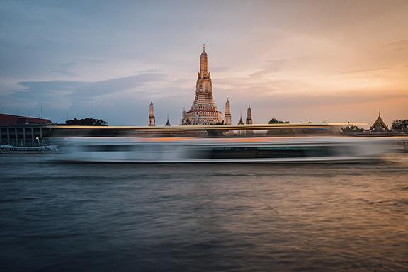 Ein verschwommenes Boot zieht seine Linien vor dem Tempel Wat Arun in Thailand.