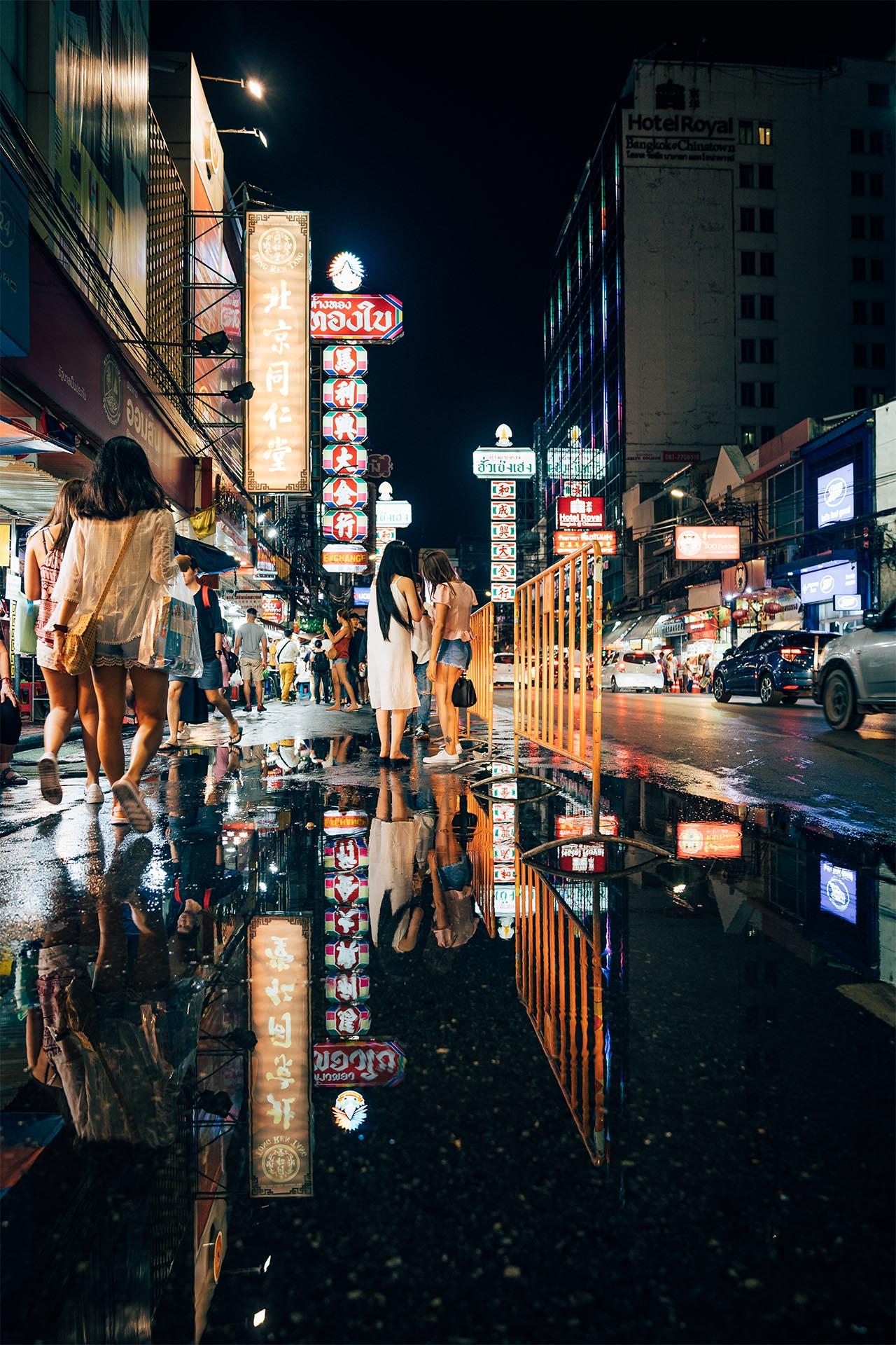 Zwei thailandische Mädchen spiegeln sich in einer Pfütze in China Town, Bangkok, Thailand.
